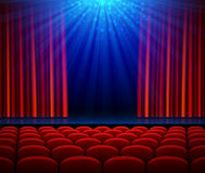 Empty theater stage with red opening curtain, spotlight and seats Royalty Free Stock Images
