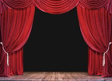 Empty theater stage with wood plank floor and open red curtains