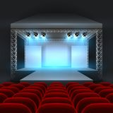 Empty theatre stage with spotlight lighting. Concert hall with podium and red seats rows. Show concert stage, podium interior for conference and performance Stock Photos