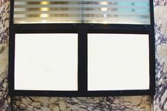 Empty thin glass showcase with lights on a marble wall. Empty thin glass showcase with lights and black frame on a marble wall Stock Images