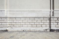 Empty tiled stone sidewalk and white ancient wall. With molding royalty free stock image