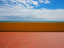 Empty tiled terracotta terrace with a yellow concrete fence at the end, in front to the sea and cloudy sky Royalty Free Stock Photography