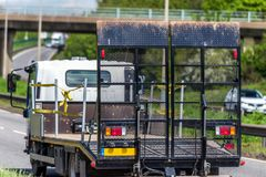 Empty tilt trailer truck on uk motorway in fast motion.  stock photography