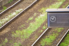 Empty time table with clock at rail tracks Stock Photo