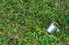 Empty tin can on the grass, human negligence royalty free stock image