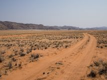 Empty tire track dirt road in Namib desert with mountains, Damaraland, Namibia, Southern Africa stock photography