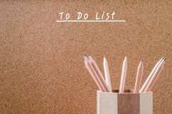 Empty to do list with pencils in wooden holder on brown backgrou. Nd Royalty Free Stock Photo