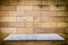 Empty top of natural stone shelves on the old grunge wall background Stock Photos