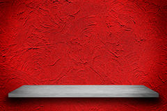 Empty top of white shelves on red wall with bright center spotli Stock Images