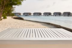 Empty top of white wooden table for product placement and display. Blue lagoon with water bungalows and tropical plants. On background Royalty Free Stock Photos