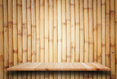 Empty top wooden shelves and bamboo wall background Stock Photos
