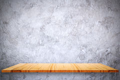 Empty top of wooden shelves and bare cement wall background. Stock Photos