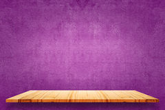 Empty top of wooden shelves and purple cement wall background. Stock Photo