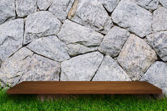 Empty top of wooden shelves on Stone Brick wall and green grass. For product display. for put product on shelves Royalty Free Stock Images