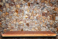 Empty top wooden shelves and stone wall background Royalty Free Stock Photos