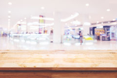 Empty top of wooden table with blur shopping mall background. Stock Photography