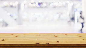 Empty top of wooden table with blur shopping mall background. Royalty Free Stock Images