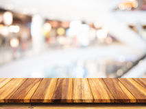 Empty top of wooden table with blur shopping mall background. Royalty Free Stock Photo