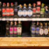 Empty top of wooden table with blurred counter bar and bottles B. Empty top wooden table with blurred counter bar and bottles Background. For display or montage stock photo