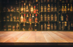 Empty the top of wooden table with blurred counter bar. And bottles Background /for your product display stock image