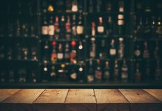 Empty the top of wooden table with blurred counter bar and bottles