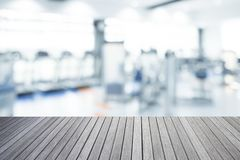 Empty top of wooden table and blurred of fitness gym background