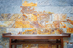 Empty top wooden table and natural stone wall background royalty free stock photo