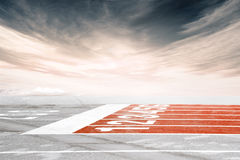 Empty track finish line against dramatic cloudy sky. An empty finish line on orange running track shot from the ground against dramatic reddish gray cloudy sky Royalty Free Stock Image
