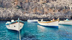 Empty traditional Maltese boats Luzzu. The empty traditional Maltese boats Luzzu in the Blue Grotto Bay. Tourism low season concept Royalty Free Stock Photography