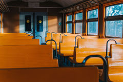 Empty train car without passengers at sunset. Empty train car with yellow seat seats without passengers at sunset Royalty Free Stock Image