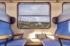 Empty train compartment with view on quaint landscape Royalty Free Stock Photos