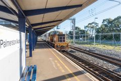 An empty train station in Palmerston North New Zealand. With a train approaching in the evening light royalty free stock images