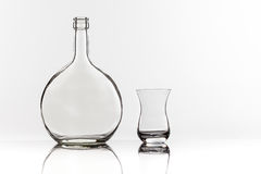 Empty transparent bottle and glass. On a reflective tile is an empty transparent bottle and glass Stock Image