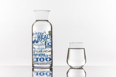 Empty transparent bottle and glass. On a reflective tile is an empty transparent bottle and glass Stock Images