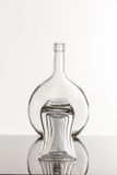 Empty transparent bottle and glass. On a reflective tile is an empty transparent bottle and glass Stock Photo