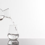 Empty transparent bottle and glass. On a reflective tile is an empty transparent bottle and glass Royalty Free Stock Photos