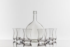 Empty transparent bottle and glass. On a reflective tile is an empty transparent bottle and glass Royalty Free Stock Photo