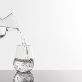 Empty transparent bottle and glass. On a reflective tile is an empty transparent bottle and glass Royalty Free Stock Image