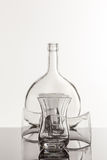 Empty transparent bottle and glass. On a reflective tile is an empty transparent bottle and glass Royalty Free Stock Photography