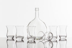Empty transparent bottle and glass. On a reflective tile is an empty transparent bottle and glass Stock Photos