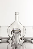 Empty transparent bottle and glass. On a reflective tile is an empty transparent bottle and glass Stock Photography