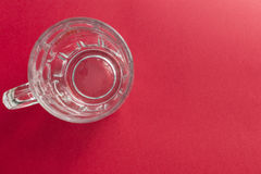 Empty and transparent glass beer jar on a red background Royalty Free Stock Photo
