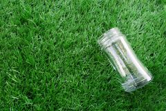 Empty transparent glass bottle lay down on the grass. Empty transparent glass bottle lay down on the artificial grass stock photos