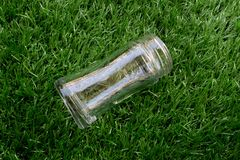 Empty transparent glass bottle lay down on the grass. Empty transparent glass bottle lay down on the artificial grass stock photo