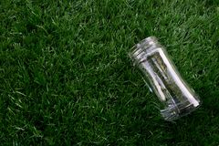 Empty transparent glass bottle lay down on the grass. Empty transparent glass bottle lay down on the artificial grass royalty free stock photography