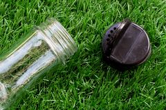 Empty transparent glass bottle of pepper with black flip up of l. Id lay down on the artificial grass stock photos