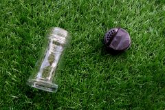 Empty transparent glass bottle of pepper with black flip up of l. Id lay down on the artificial grass stock photography