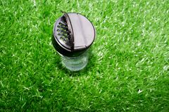Empty transparent glass bottle of pepper. Set up on the artificial grass royalty free stock photo