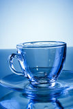 Empty transparent glass mug on blue background Stock Photos