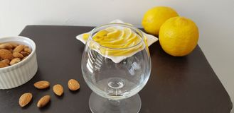 Empty transparent vine glass on brown table near roasted almonds and lemons royalty free stock photos